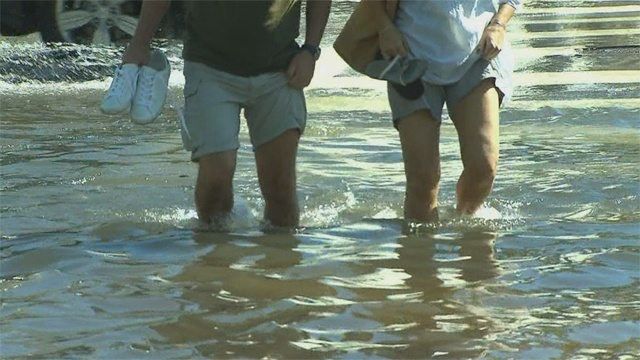 People walking through floodwaters on South Beach