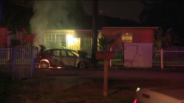 Car burns next to pole outside northwest Miami-Dade home