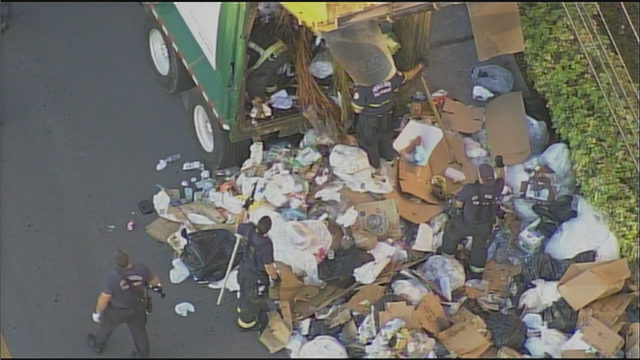 Firefighters sift through trash after noise heard inside compactor