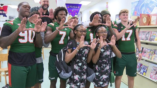 UM football players handed backpacks to Liberty City students
