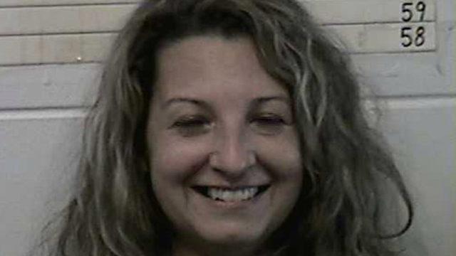 Woman smiles wide after arrest for husband's murder
